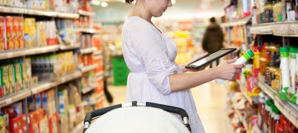 Woman comparing products with a tablet comptuer in a supermarket